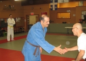 George shaking hands with his technical instructor Sensei Rejean after receiving his Brown belt